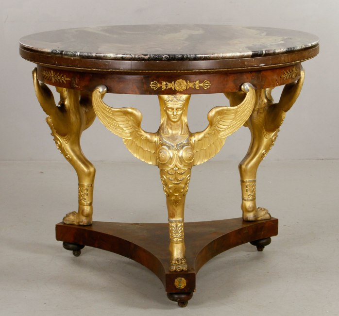 French Empire Style mahogany and ormolu center table, the three standards modeled as winged caryatid terms on lion claw feet, the apron embellished with bronze paterae detailed with anthemion sprays and laurel